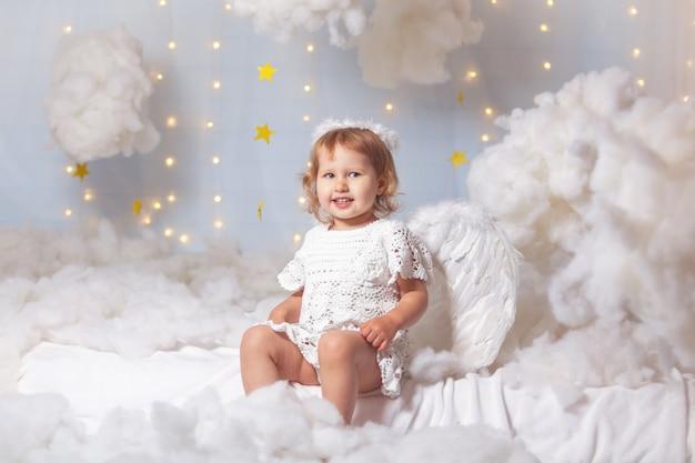 Criança anjo está sentado as nuvens olha para baixo