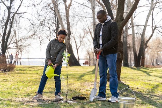 Criança aprendendo a plantar uma árvore