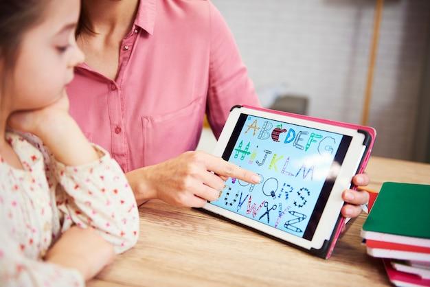 Criança aprendendo o alfabeto no tablet