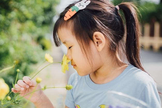 Criança aprendendo o sentido do olfato da flor