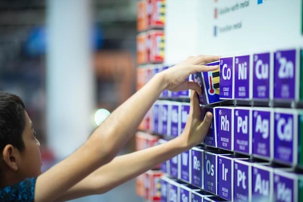 Criança aprendendo tabela periódica na sala de aula na escola