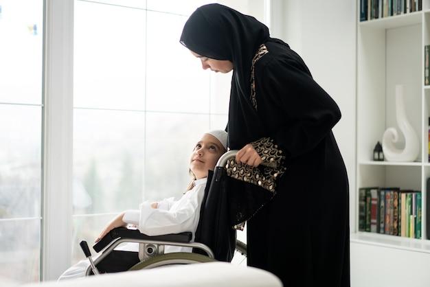 Criança árabe com cadeira de rodas e mãe em casa