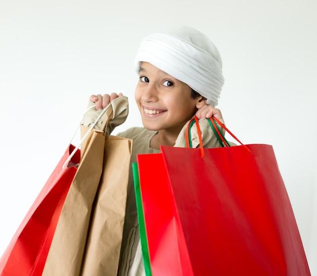 Criança árabe com sacolas de compras