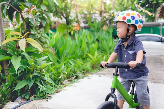 Criança asiática, andar bicicleta