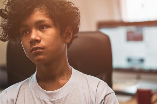 Criança asiática assustada e sozinha, com alto risco de sofrer bullying, tráfico e abuso, foco seletivo