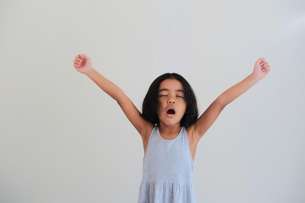 Criança asiática bocejando depois de acordar de manhã