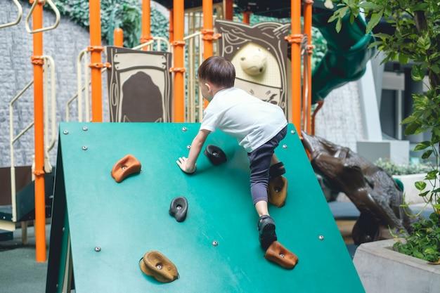 Criança asiática bonita de 2 a 3 anos se divertindo tentando escalar pedras artificiais no playground, garotinho subindo uma parede de pedra, coordenação de mãos e olhos, desenvolvimento de habilidades motoras