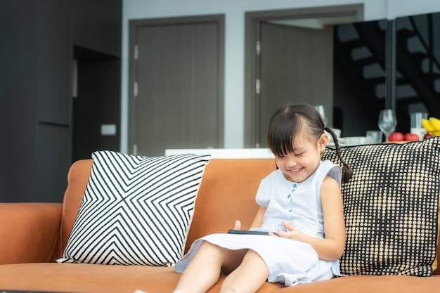 Criança asiática bonita usando um smartphone