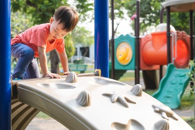 Criança asiática bonito da criança se divertindo tentando subir em pedregulhos artificiais no playground, garotinho subindo uma parede de pedra, coordenação de mãos e olhos, desenvolvimento de habilidades motoras