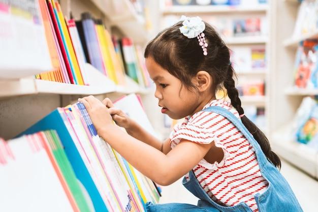 Criança asiática bonito menina selecione o livro na estante na livraria no supermercado