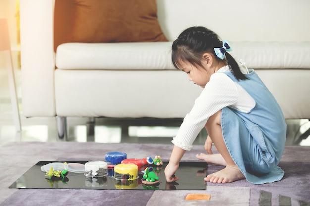 Criança asiática brincando sozinha em sua casa