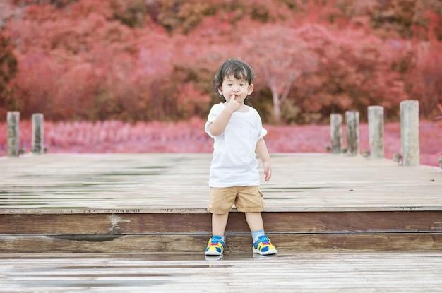 Criança asiática closeup ficar no caminho de madeira no fundo do parque