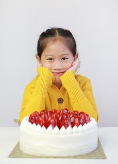 Criança asiática com bolo de morango