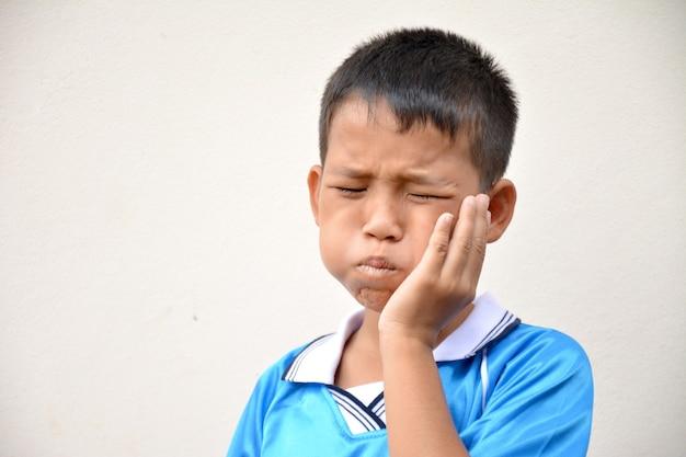 Criança asiática com dor de dente segurando a bochecha