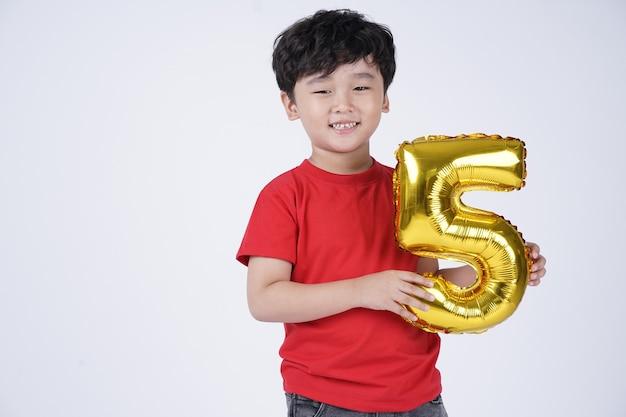 Criança asiática com sorriso feliz com balão de papel alumínio, isolado no fundo branco