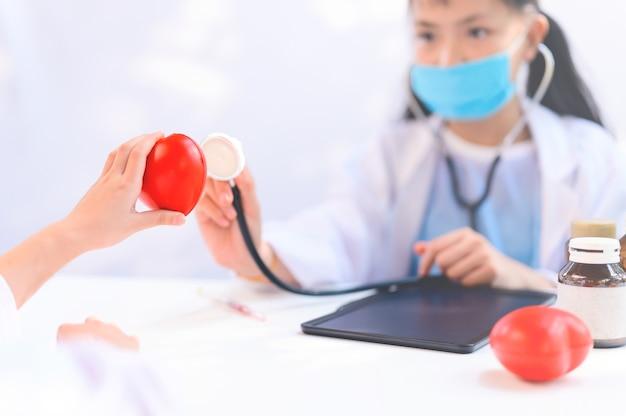 Criança asiática como médico e o conceito de cuidados de saúde. bem-estar e autocuidado. as crianças sonham com o emprego quando crescerem para ajudar as pessoas a parar o coronavirus.