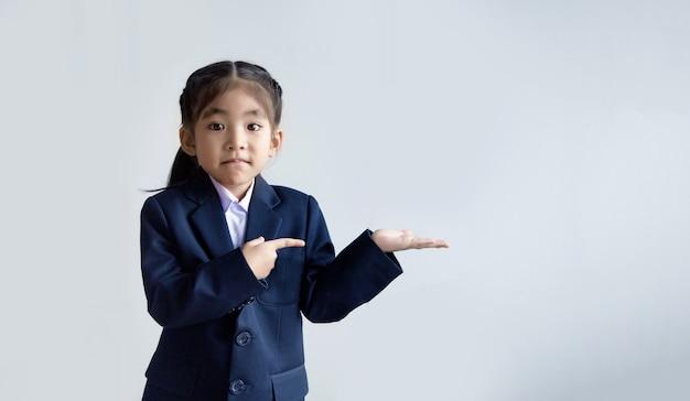 Criança asiática confiante em uniforme com a mão aberta e apontando para apresentar no espaço