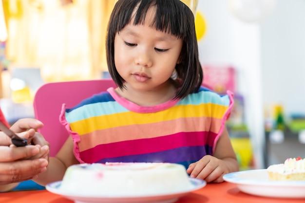 Criança asiática cortando bolo de aniversário para comemorar