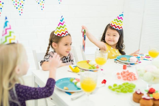 Criança asiática dando guardanapo de papel para aniversariante