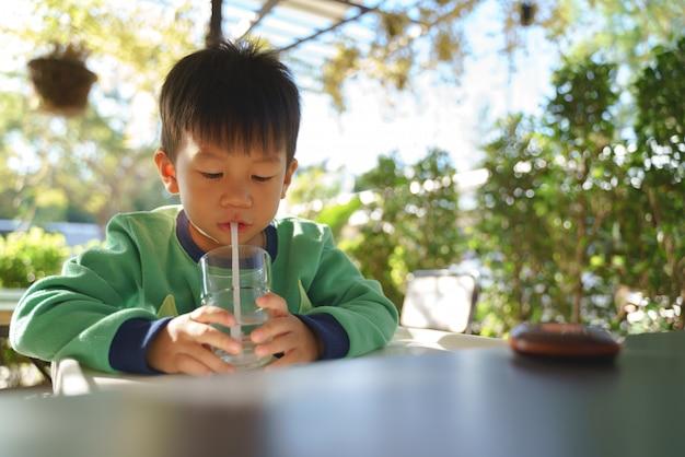 Criança asiática de 3 anos de idade bebendo água