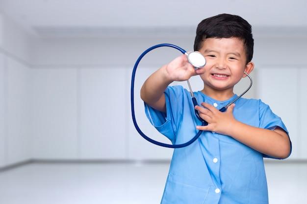 Criança asiática de sorriso no uniforme médico azul que guarda o estetoscópio que olha a câmera, conceito saudável.