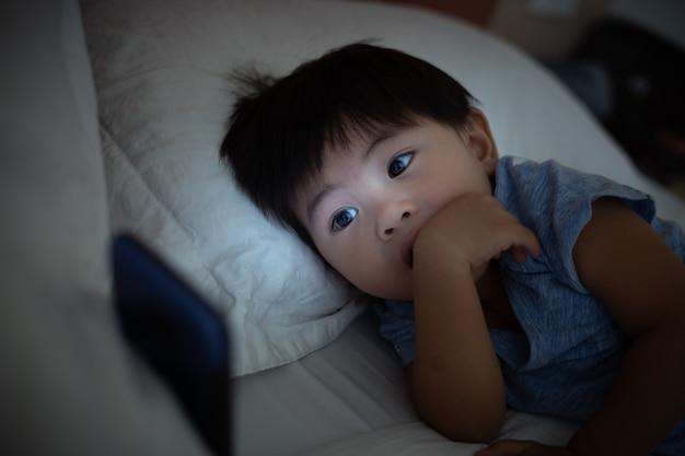 Criança asiática deitada na cama e jogando no celular