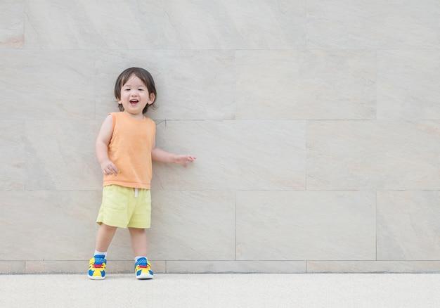 Criança asiática do close up com a cara do sorriso na parede de mármore textured