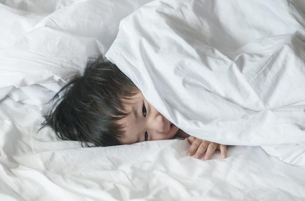 Criança asiática do close up na cama com a cara do sorriso na manhã
