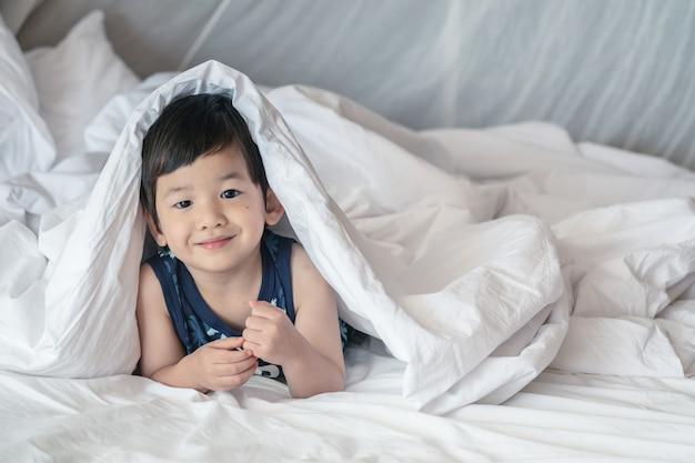 Criança asiática do close up na cama sob o cobertor com a cara do sorriso na manhã