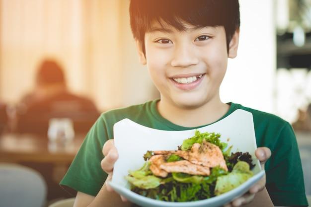 Criança asiática do estilo de vida saudável que mostra o sorriso da salada.