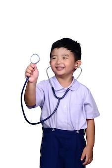 Criança asiática do estudante na farda da escola que joga o estetoscópio médico com trajeto de grampeamento.