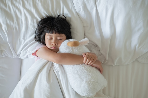Criança asiática dormindo na cama, criança doente