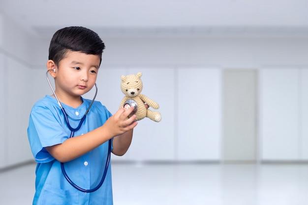 Criança asiática em uniforme médico azul com estetoscópio