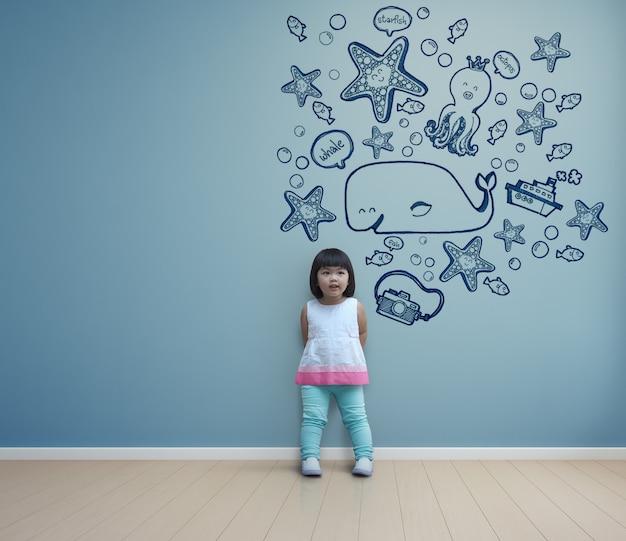 Criança asiática engraçada que joga na sala azul em casa.