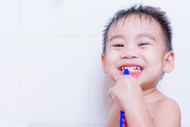 Criança asiática escova os dentes com creme dental na boca
