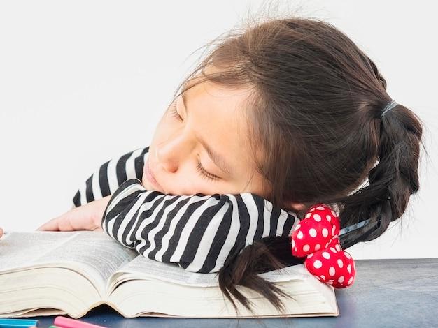 Criança asiática está dormindo durante a leitura de um grande livro