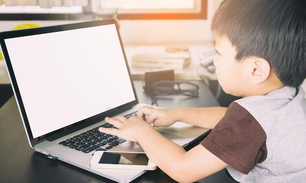 Criança asiática está usando um laptop com tela em branco para mock up