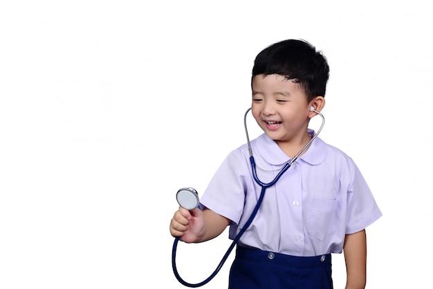 Criança asiática estudante de jardim de infância tocando estetoscópio médico