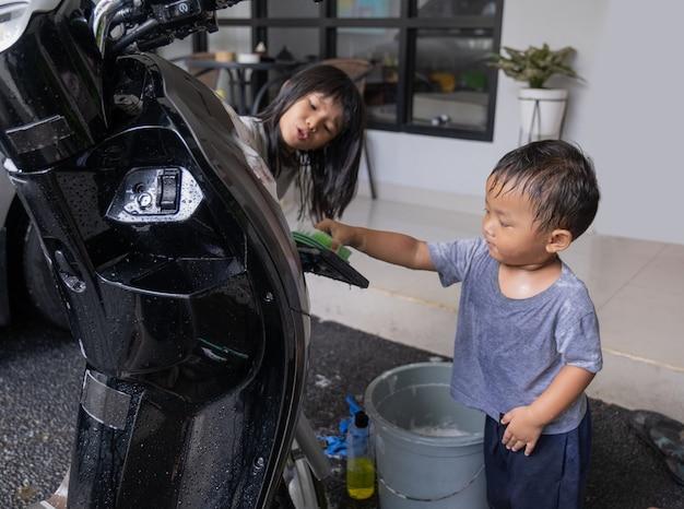 Criança asiática feliz brincando e lavando scooter de moto em casa