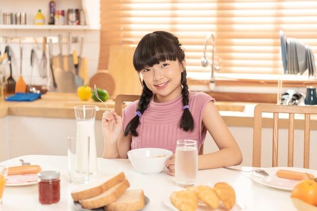 Criança asiática feliz comendo cereais e leite café da manhã na sala de cozinha em casa.