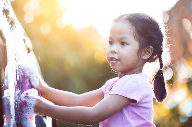 Criança asiática feliz, se divertindo para ajudar os pais a lavar o carro com a luz solar