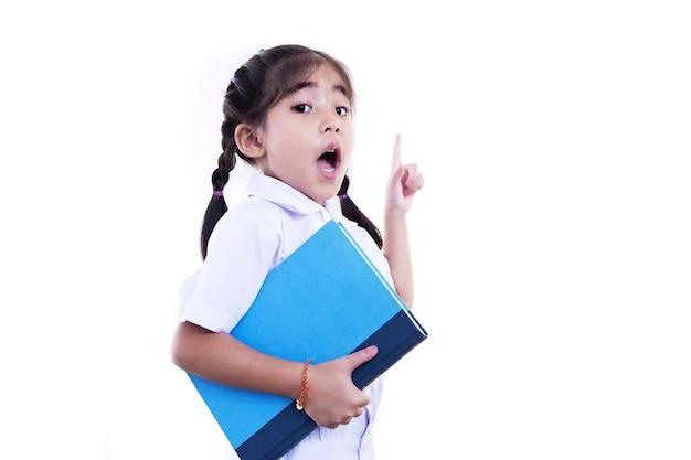 Criança asiática feliz segurando o livro e apontando o dedo para cima enquanto tenho uma ideia em uniforme de estudante