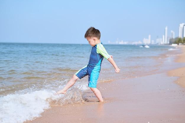 Criança asiática fofa chutando as ondas do mar na praia