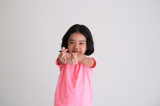Criança asiática fofa sorrindo enquanto mostra o símbolo do dedo do amor