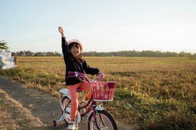 Criança asiática independente andando de bicicleta