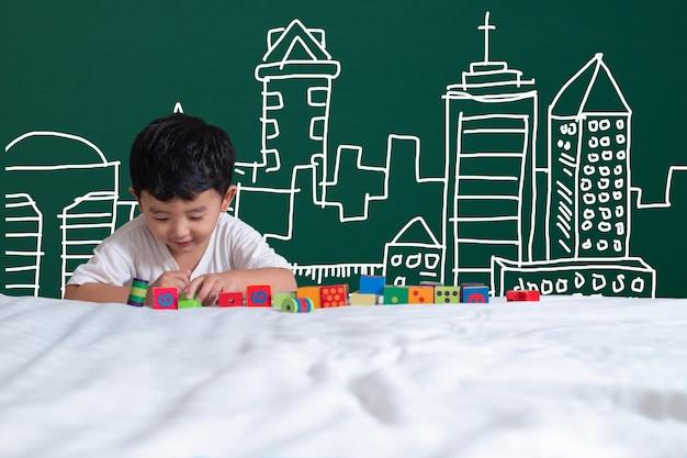 Criança asiática, jogando brinquedo, com, predios, arquitetura, desenho, mão, desenhado