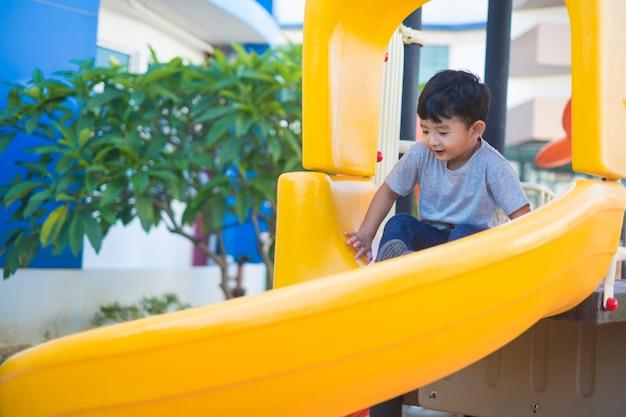 Criança asiática jogando slide no playground