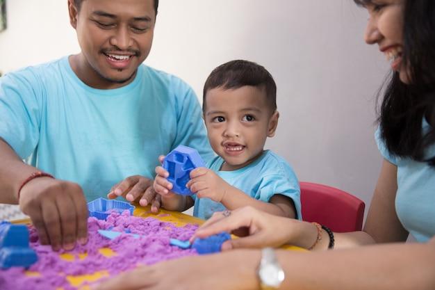 Criança asiática jogar areia interior