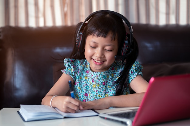 Criança asiática menina bonitinha estudando lição on-line em casa, distância social durante a quarentena, o conceito de educação on-line
