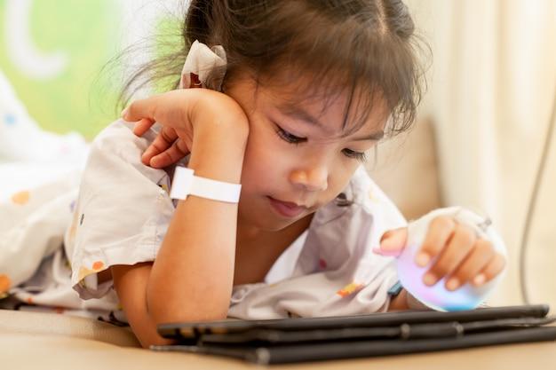 Criança asiática menina doente que tem solução intravenosa enfaixada jogando tablet digital